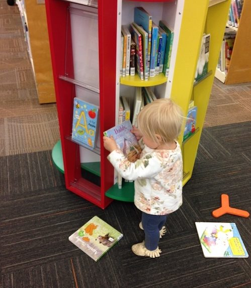 Toddler with board books in library