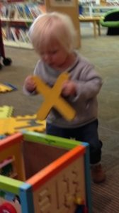 Toddler playing with letter X in Library